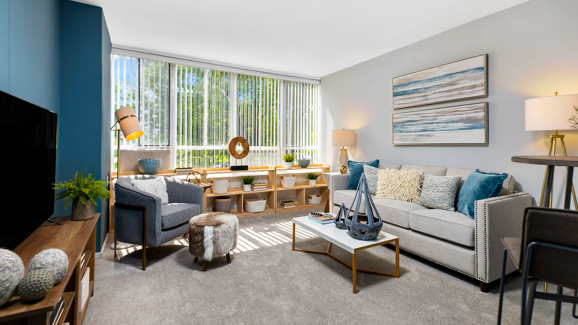 A living room in a 1-bedroom residence at Lake Meadows. A couch and coffee table are along the right wall with a chair and television opposite. Trees and blue sky can bee seen out the window.