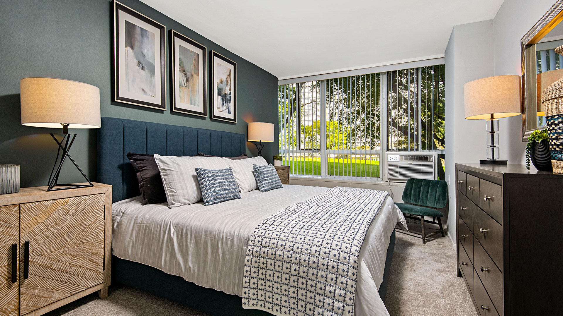 A high-rise bedroom at Lake Meadows with a large bed and night stands across from a large dresser. Trees and a green park can be seen out the window.