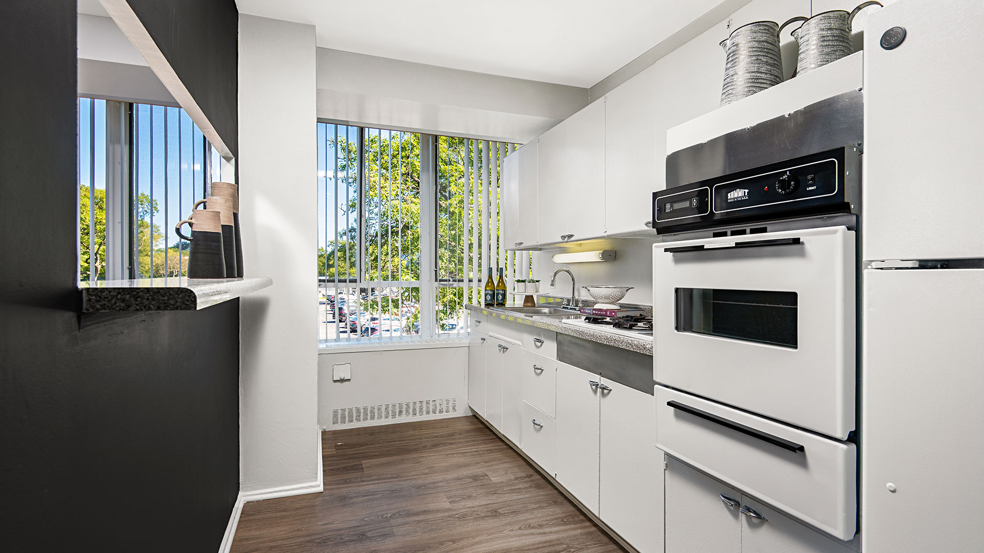 A look through the kitchen of a 3-bedroom, high-rise residence at Lake Meadows. White cabinets and appliances line the right wall, with a serving window on the left. Trees and blue skies are seen out the window.