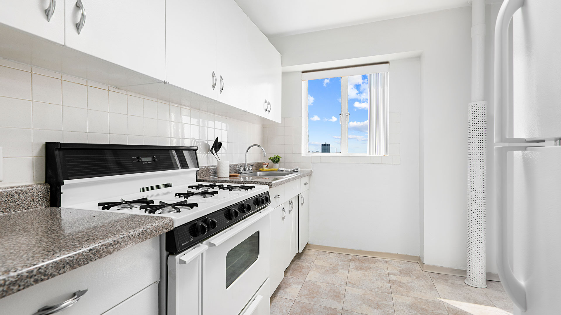 A standard kitchen in a Lake Meadow mid-rise residence with white cabinets and appliances. A bright blue sky with a few clouds is seen out the window.