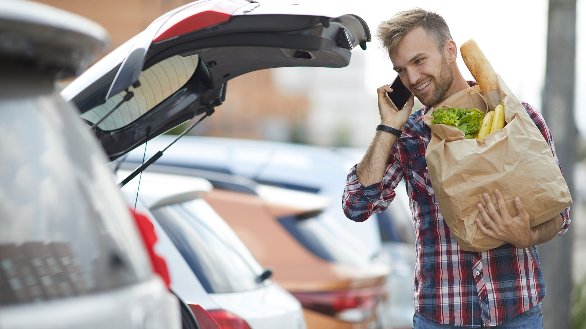A man gets groceries out of his hatchback with talking on a mobile phone.
